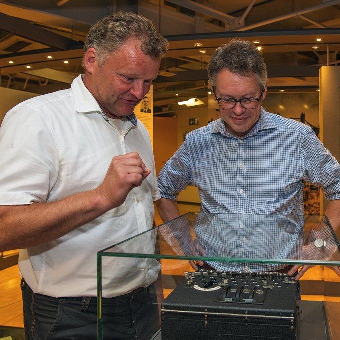 Dermot Turing with Jochen Viehoff viewing an Enigma machine