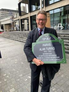 Dermot Turing with a plaque for the Parvis Alan Turing