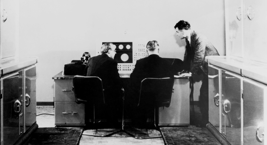 Alan Turing (standing) with colleagues working on the Manchester Mark 1 computer